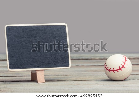 an empty, copy space chalkboard/blackboard/sign standing next to a miniature/toy baseball. sports and exercise, concept image. wood panels and grey background.