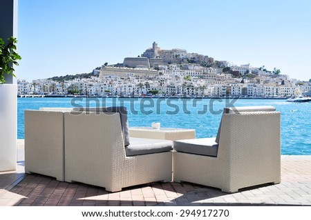 an empty couch at the Mediterranean Sea, with Sa Penya and Dalt Vila districts, the old town of Ibiza Town, in the background, in the Balearic Islands, Spain - stock photo