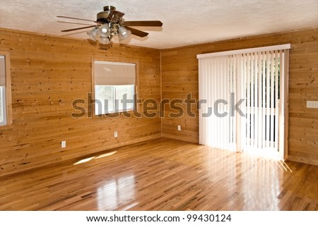 An empty den or living area in a house with pine walls,oak flooring and vertical blinds. - stock photo
