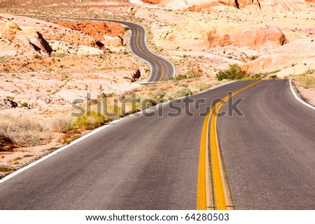 An empty desert highway winds through sandstone rock formations in Nevada - stock photo