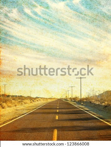 An empty desert road in Arizona's Mojave desert with grunge stains and spots.  Image has a distinct paper texture visible at 100%. - stock photo