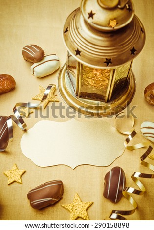 An empty golden seal to write headline. Ramadan lamp, date chocolates and confetti background. - stock photo