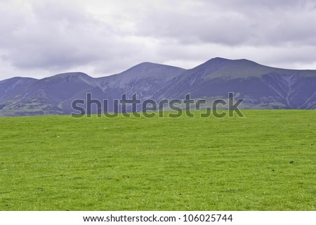 An empty green hill with mountains on the background in a cloudy day. Lake district, UK - stock photo