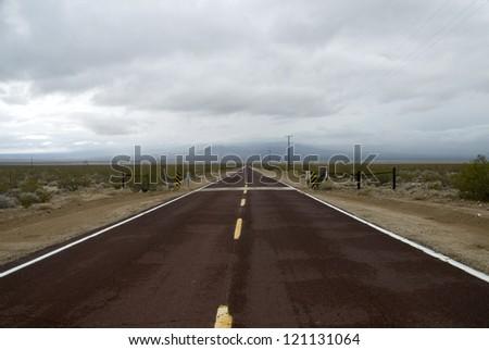 An empty highway through a bleak Nevada landscape. - stock photo