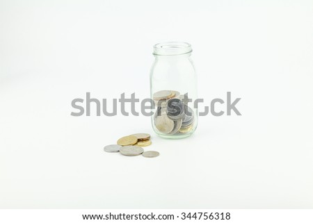 An empty label of glass jars with coins on white background - savings, financial, loan, retirement, and home concept - stock photo