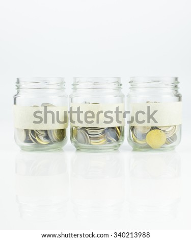 An empty label of glass jars with coins over white background - stock photo