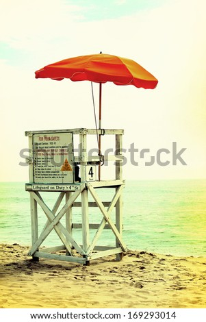 An empty lifeguard tower overlooking the ocean at the beach. Vintage photograph effects. - stock photo