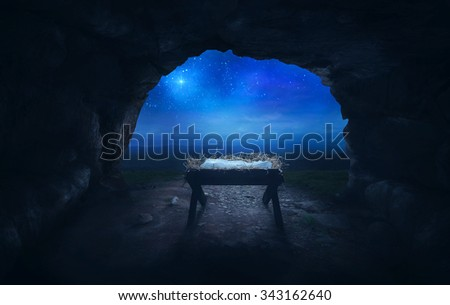An empty manger inside a cave under the star of Bethlehem. - stock photo