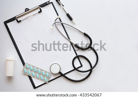 An empty medical file with stethoscope and pen on top of it,next to several medications. Negative space on right side. Top view.