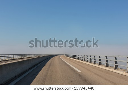 An empty open road on a bridge on a slightly foggy day but with a blue sky
