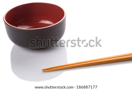 An empty red and black bowl with a pair of chopsticks over white background