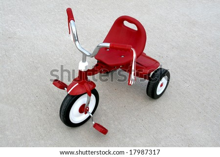 an empty red tricycle on a cement background - stock photo