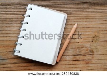 An empty retro notebook with old paper and little pencil - stock photo