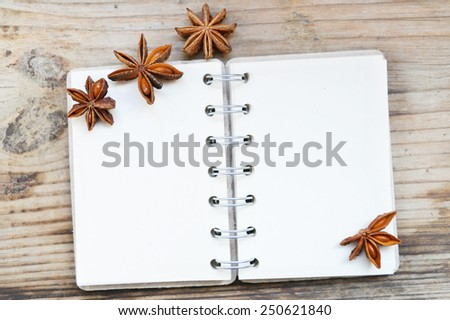 An empty retro spiral notebook with old paper and anise stars on wooden table - stock photo