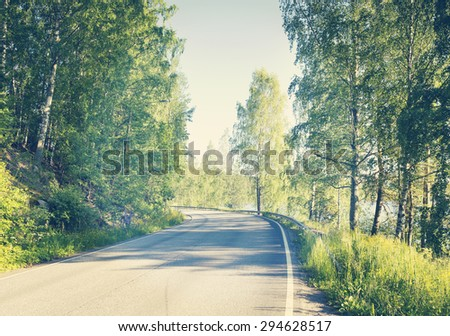 An empty road in the summer time. Image has a vintage effect.