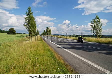 An empty road lined with poplar alley in the countryside, passing motorcycle, in the background green field, forest and mountain - stock photo