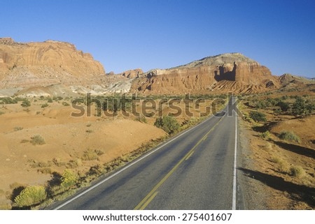 An empty road runs through red rock in the desert southwest USA