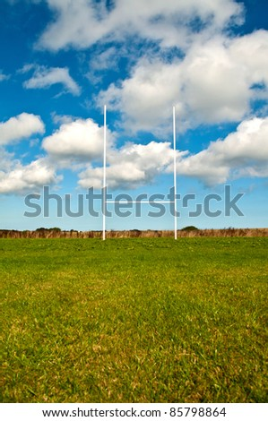 An empty rugby field with a blue sky - stock photo