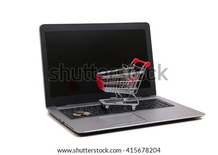 An empty shopping cart with euro coins are lying on keyboard of notebook