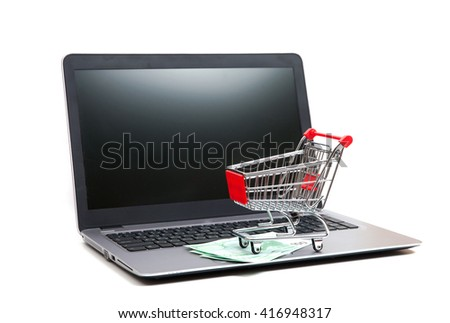 An empty shopping cart with three hundred euros on keyboard of laptop