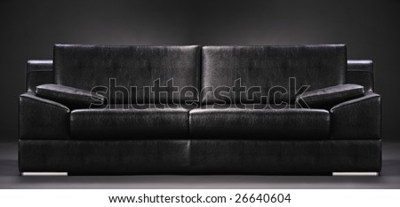 An empty sofa isolated on a black background - stock photo
