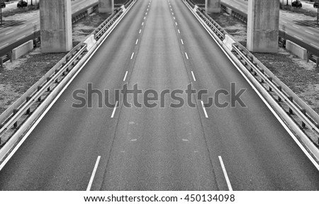 An empty three lane carriageway, processed in monochrome.