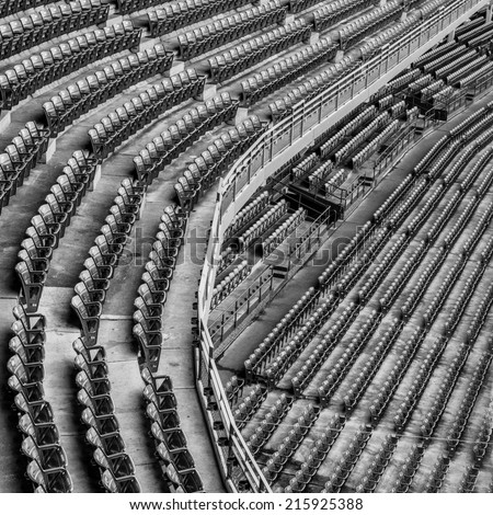 An empty upper and lower deck of an old stadium in black and white - stock photo