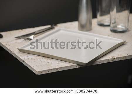 An empty white square dining plate or tray alongside dinner knife and fork, salt shaker, and a pair of drinking glasses all on a stone countertop.