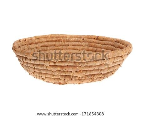 An empty wicker dish on white background. Traditional rustic handmade product.