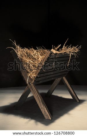 An empty wooden manger filled with hay. - stock photo