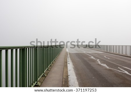 an endless road in fog on a bridge