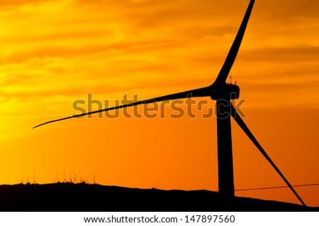 An energy generating wind turbine in Palm Springs at sunset. - stock photo