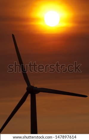 An energy generating wind turbine in Palm Springs.  There were fires nearby, which created the orange sky effect. - stock photo