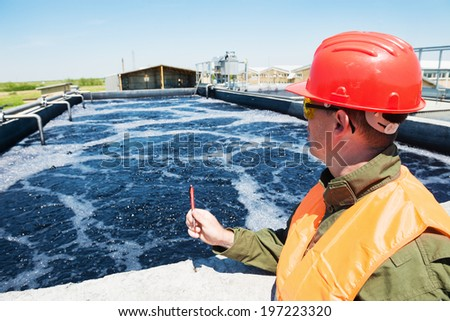 An engineer controlling a quality of water ,aerated activated sludge tank at a waste water treatment plant - stock photo