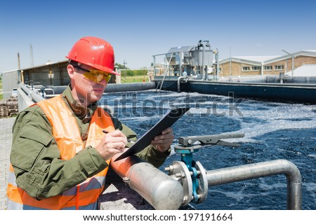 An engineer controlling the quality of water , aerated activated sludge tank at a waste water treatment plant - stock photo