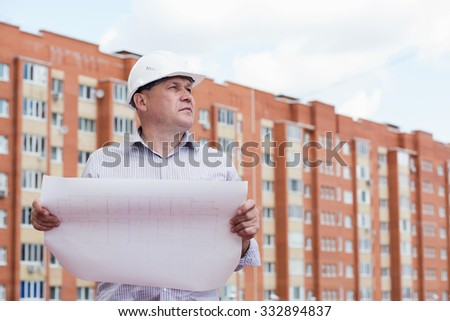 An engineer examining blueprints on a background with buildings