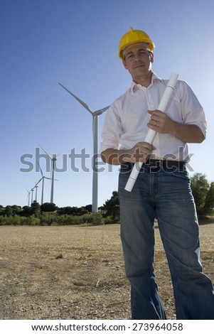 An engineer holds blueprints with wind turbines in the background.