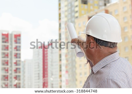 An engineer in white helmet pointing on blueprints on buildings on a background