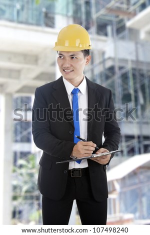 An engineer on construction site checks details on a clipboard. - stock photo