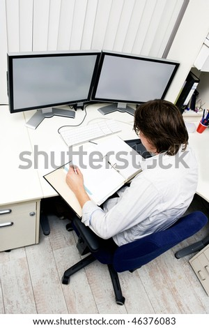 an engineer studying a thick dossier behind his desk with two computer screens on it - stock photo