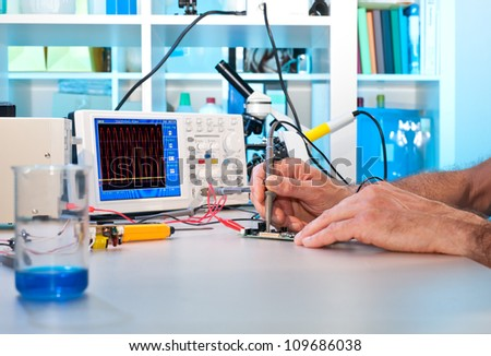 An engineer tests electronic components with oscilloscope in the service centre - stock photo