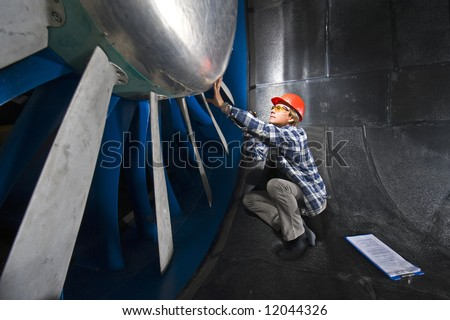 An engineer, wearing the appropriate protective gear, examining the rotor of an industrial wind tunnel facility - stock photo