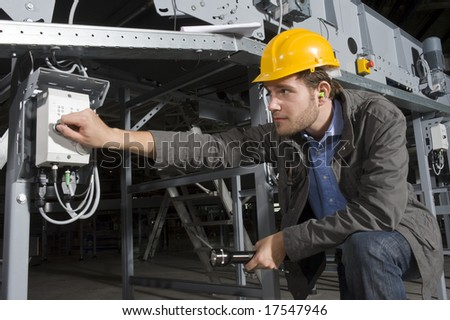 An engineer, wearing the proper safety equipment, turning on a machine by twisting a knob
