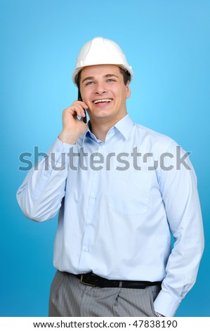 An engineer with blue hard hat talking on his mobile phone on blue background