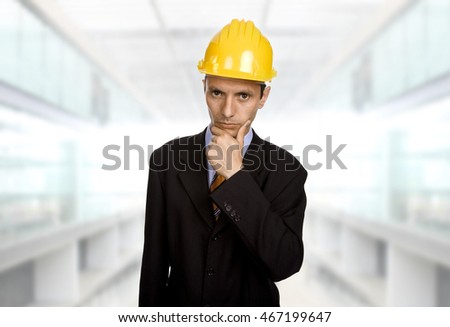 An engineer with yellow hat thinking at the office