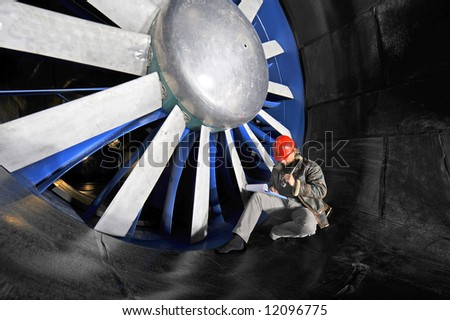 An engineer working through a checklist on a clipboard in front of the huge blades of a wind tunnel - stock photo