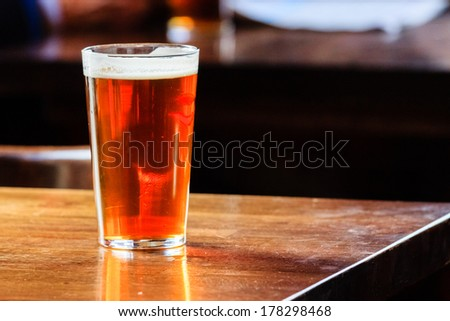 An english ale on a wooden table in a pub in London, UK - stock photo