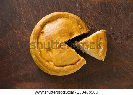 An English artisan Melton Mowbray pork pie, with a wedge cut out on a dark wood chopping board, taken from above with copy space.