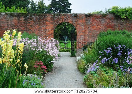 An English Landscape garden with colorful borders of Summer flowers and arch through a wall - stock photo
