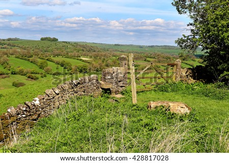 An English Rural Landscape in the Derbyshire Peak district with five bar gate, signpost and stile
